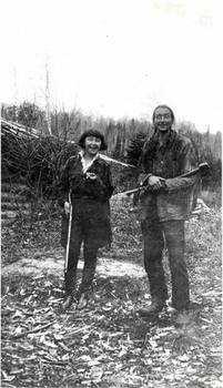 Grey Owl and Anahareo at Squatech, Temiscouata holding shot gun and ax, 1929. Credit: University of Saskatchewan Archives, JGD/MG01/XVII/JGD 2802.
